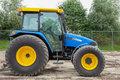 Blue tractor yellow with the sky and trees as background Royalty Free Stock Photography