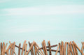 Blue or turquoise oceanic background with a fence of driftwood f