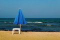 The blue umbrella a solitary beach and a white plastic table on a sandy beach close to water s edge Stock Image