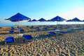 Blue umbrellas and chaise longue on empty sandy beach greece in the morning crete Stock Photos