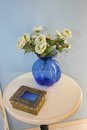 Blue vase with white flowers at night table Stock Image