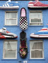 A blue wall with loads of shoes many hanging on Royalty Free Stock Image
