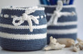 Blue and white pen holder storage jars covered with crochet cover next to corals for a maritime design feeling Royalty Free Stock Image