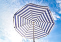 Blue and white sun beach umbrella and blue sky with clouds Royalty Free Stock Photo