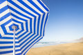 Blue and white sunshade travel background with a at an endless beach with a sky a turquoise sea playa de las pilas Royalty Free Stock Photo