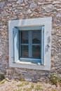 Blue and white window on an old greek house made of stone, Panormos bay, Skopelos island Royalty Free Stock Photo
