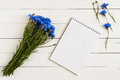 Blue wildflowers beautiful bouquet of with a notebook for notes on a white wooden table Royalty Free Stock Image