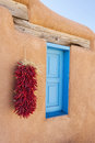 Blue window chili pepper ristra adobe wall new mexico Royalty Free Stock Image