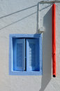Blue window and red rainwater pipe with shutters downpipe of the white greek traditional house Stock Photos