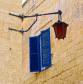 Blue window shutters and dark orange antique lantern on background of yellow brick walls Royalty Free Stock Images