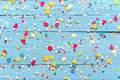 Blue wood background with scattered party confetti Royalty Free Stock Photo
