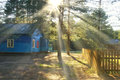 Blue wooden cottage house with sun rays Royalty Free Stock Image
