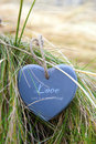 Blue wooden love heart on beach single in dunes an irish Stock Photos