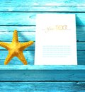 On blue wooden texture yellow starfish and a white sheet of paper are on the shelf in the background. Royalty Free Stock Photo