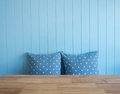 Blue wooden wall background with polkadot pillows and foreground is table composition space for text Stock Photo