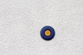 Blue and yellow button abstract view of on mortar finished wall Stock Photo