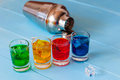 Blue yellow green red alcohol or alcohol free cocktail with ice cubes and shaker on a bar counter wooden background Stock Image