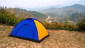 Blue and Yellow tourist camping tent in recreation area among meadow in mountain forest