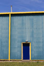 Blue and yellow warehouse building exterior of modern sky background Royalty Free Stock Photos
