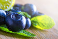 Blueberries blue and mint leaves on wooden table Stock Photo