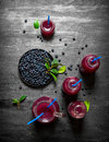 Blueberries and blueberry juice. On black wooden background. Royalty Free Stock Photo