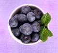 Blueberries with mint in white bowl top view on purple background close up Stock Photos