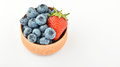 Blueberries and one strawberry in wooden bowl isolated on white Royalty Free Stock Photo