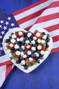 Blueberries and strawberries with cream on usa flag patriotic red white blue berries fresh whipped stars in white heart shape Stock Image