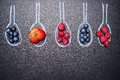 Blueberries, strawberries, raspberries, and a variety of berries, in painted chalk spoons, place  text, top view Royalty Free Stock Photo