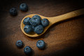 Blueberries on a wooden spoon with textured background Stock Photos