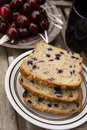 Blueberry bread with red cherries and tea on a wooden table Stock Image