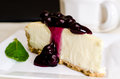 Blueberry cheesecake and coffee slice of with mint garnish shallow depth of field Royalty Free Stock Images
