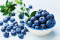 Blueberry or great bilberry in bowl on blue rustic background. Organic superfood and healthy nutrition. Royalty Free Stock Photo