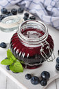 Blueberry jam in a glass jar on white wooden background Stock Images