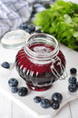 Blueberry jam in a glass jar on white wooden background Royalty Free Stock Photography