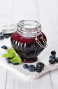 Blueberry jam in a glass jar on white wooden background Royalty Free Stock Photos