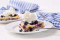 Blueberry lemon tart with whip cream on wood table Royalty Free Stock Image