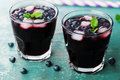 Blueberry lemonade or cocktail on teal rustic table, summer berry juice Royalty Free Stock Photo