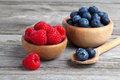 Blueberry and raspberries in bowls Stock Images