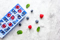 Blueberry and raspberry in ice tray on stone background top view mock-up Royalty Free Stock Photo