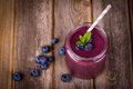 Blueberry smoothie in a glass jar with a straw and sprig of mint over vintage wood table with fresh berries Stock Photography