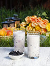 Blueberry smoothie on wooden table summer party flowers and fruits grass in the background selective focus Stock Image