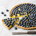 Blueberry tart with vanilla custard on a marble board. Royalty Free Stock Photo
