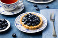 Blueberry tartlet, pie, tart with vanilla custard. Blue stone background Royalty Free Stock Photo