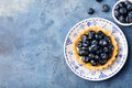 Blueberry tartlet, pie, tart with vanilla custard. Blue stone background. Top view Copy space Royalty Free Stock Photo