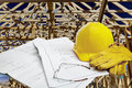 Blueprints with hardhat, workgloves, reading glasses and framed wood structure in background Royalty Free Stock Photo