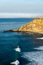 Bluff cove with surfers riding waves Royalty Free Stock Photography