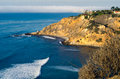 Bluff cove with surfers riding waves Stock Image