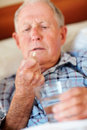 Blur image of an elderly man holding a pill in bed Royalty Free Stock Photos
