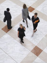 Blurred business people walking on tiled floor elevated view of Royalty Free Stock Images